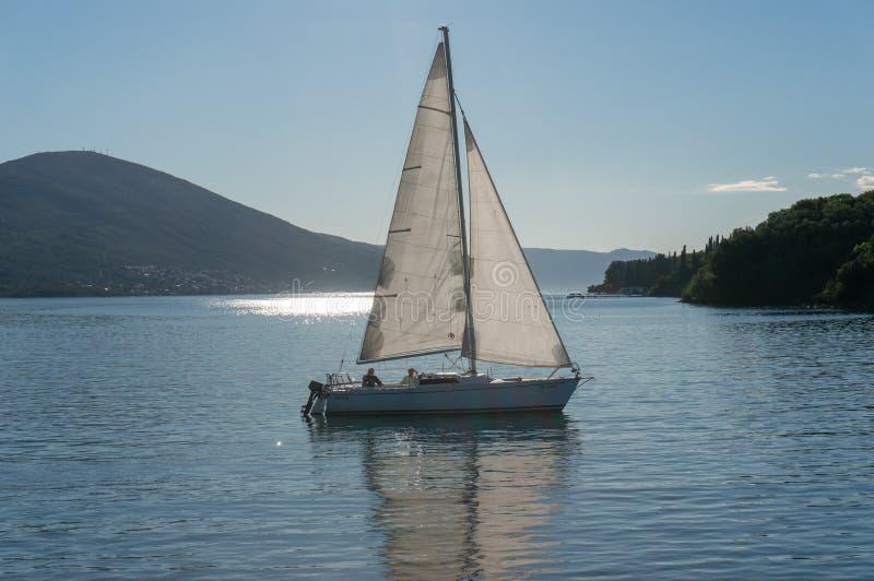 Ensam fartygsegling i fjärden av Kotor, Montenegro Sikt av det ensamma fartyget i bakgrundsbergen fotografering för bildbyråer