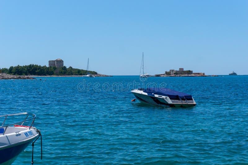 Ensam fartygsegling i fjärden av Kotor, Montenegro Sikt av det ensamma fartyget i bakgrundsbergen arkivfoton