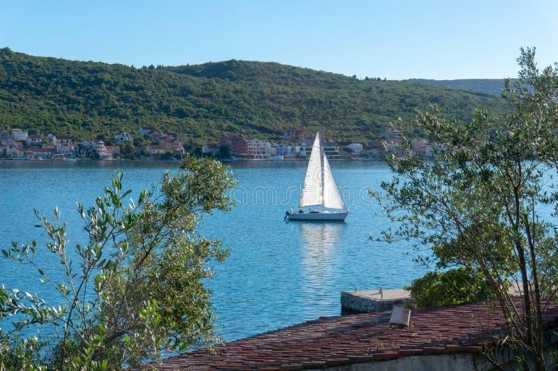 Ensam fartygsegling i fjärden av Kotor, Montenegro Sikt av det ensamma fartyget i bakgrundsbergen arkivfoto