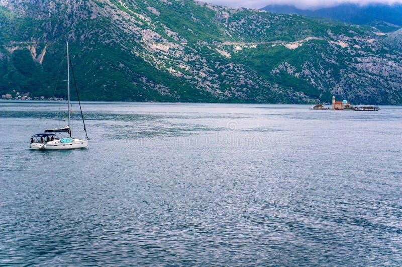 Ensam fartygsegling till fyren av oskulden av klippan i fj?rden av Kotor royaltyfri bild