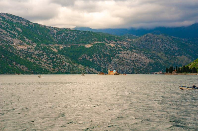 Ensam fartygsegling till fyren av oskulden av klippan i fj?rden av Kotor arkivfoto