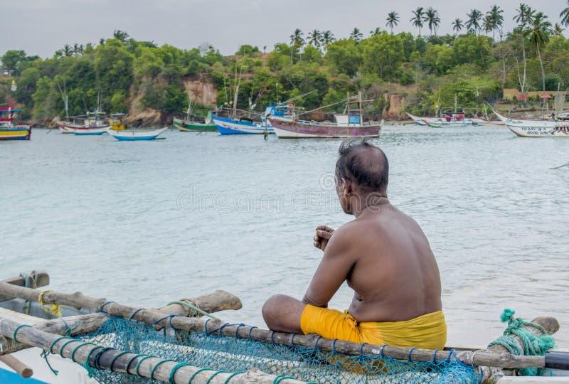 Ensam fiskare som sitter på fiskebåten royaltyfria bilder