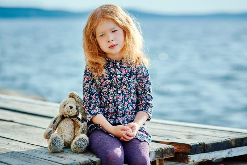 Ensam flicka med ett leksaksammanträde på en ponton nära vattnet arkivbild