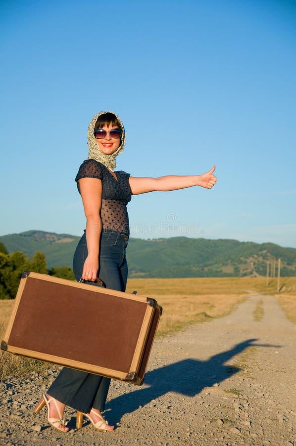 Ensam flicka med resväska royaltyfri foto