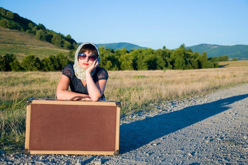 Ensam flicka med resväska arkivbild