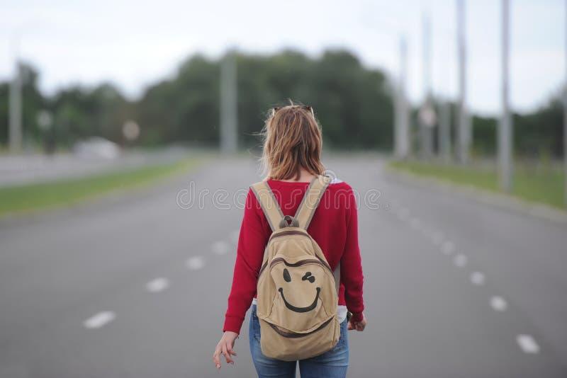 Ensam flicka som liftar på vägen med en ryggsäck arkivbilder