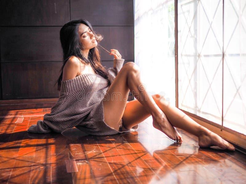 Ensam flicka som SAD sitter vid fönstret i sovrummet royaltyfria foton