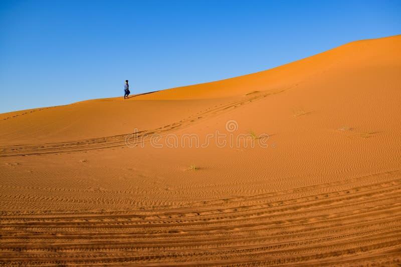 Ensam fotgängare till och med öknen som lämnar en slinga av fotspår royaltyfri bild