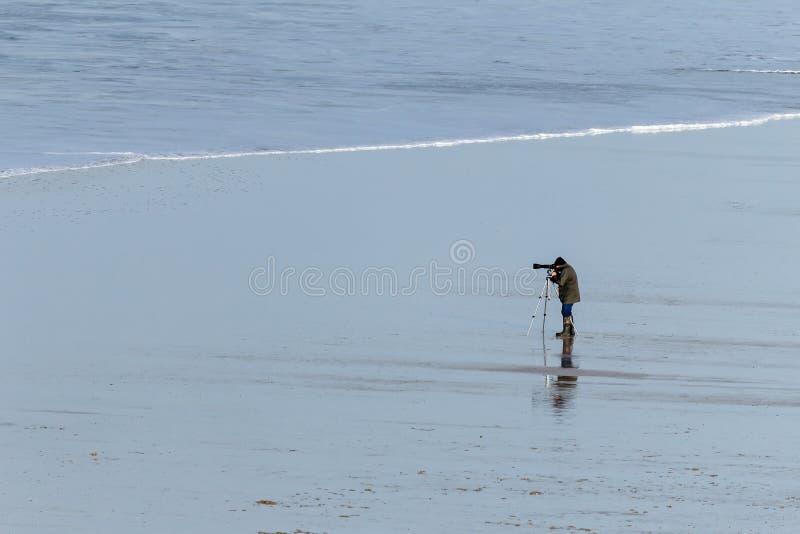 Ensam fotograf på den öde stranden i norr Cornwall arkivfoton