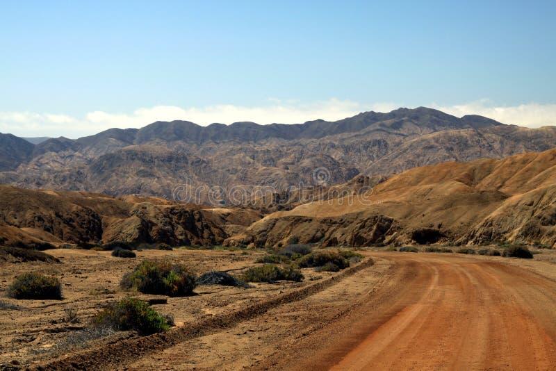 Ensam grusväg in i den karga torra dalen i den Atacama öknen, Chile fotografering för bildbyråer
