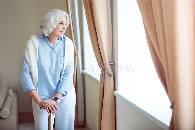 Ensam hög kvinna med kryckan royaltyfria foton