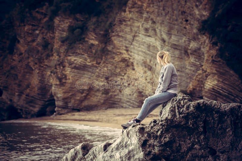 Ensam handelsresande för ung kvinna som kopplar av på en stor klippasten på stranden som ser löst berglandskap i retro tappning s royaltyfria foton
