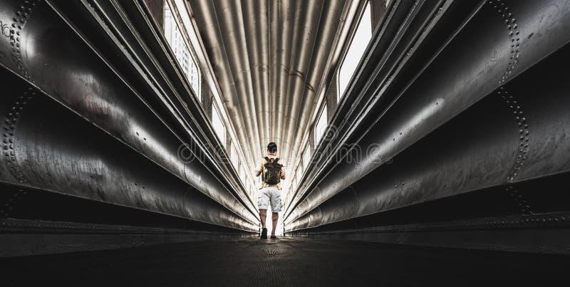 Ensam handelsresandeman med ryggsäcken som wolking i en stads- tunnel för stål - stadsturism i sällsynt sceniskt ställebegrepp -  royaltyfri fotografi
