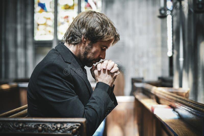 Ensam kristen man som ber i kyrkan arkivbilder