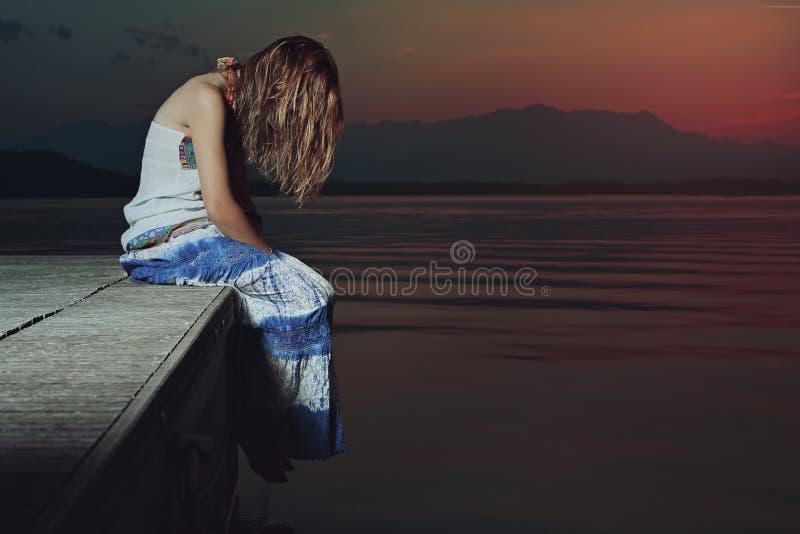 Ensam kvinna i ledsen position över sjövatten arkivfoto
