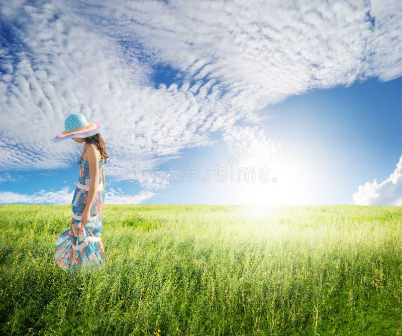 Ensam kvinna med den blåa skyen i gröna fält arkivfoton