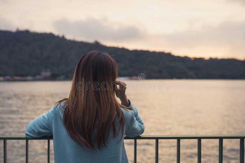 Ensam kvinna som står frånvarande sinnat på floden royaltyfri foto