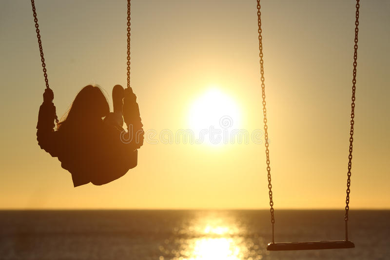 Ensam kvinnakontur som svänger på solnedgången på stranden royaltyfri fotografi