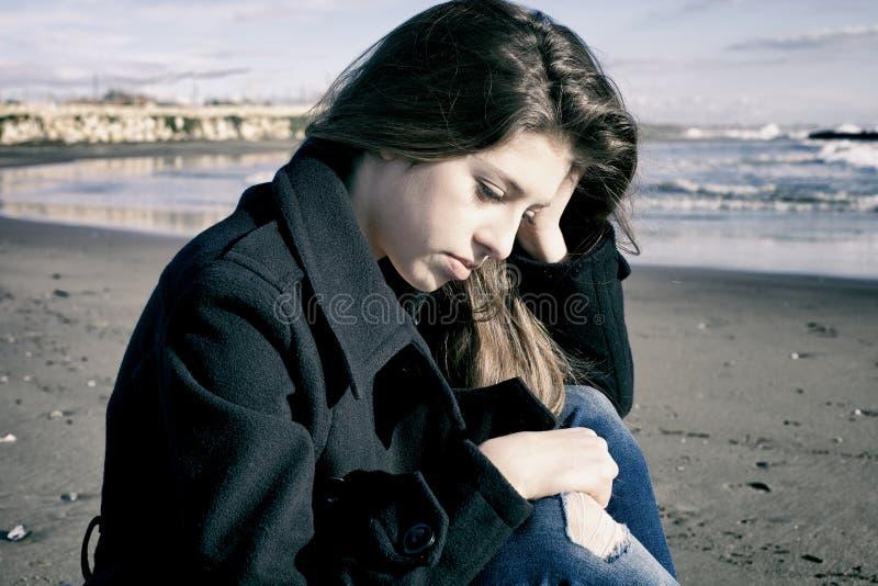 Ensam ledsen flicka framme av havet arkivfoton
