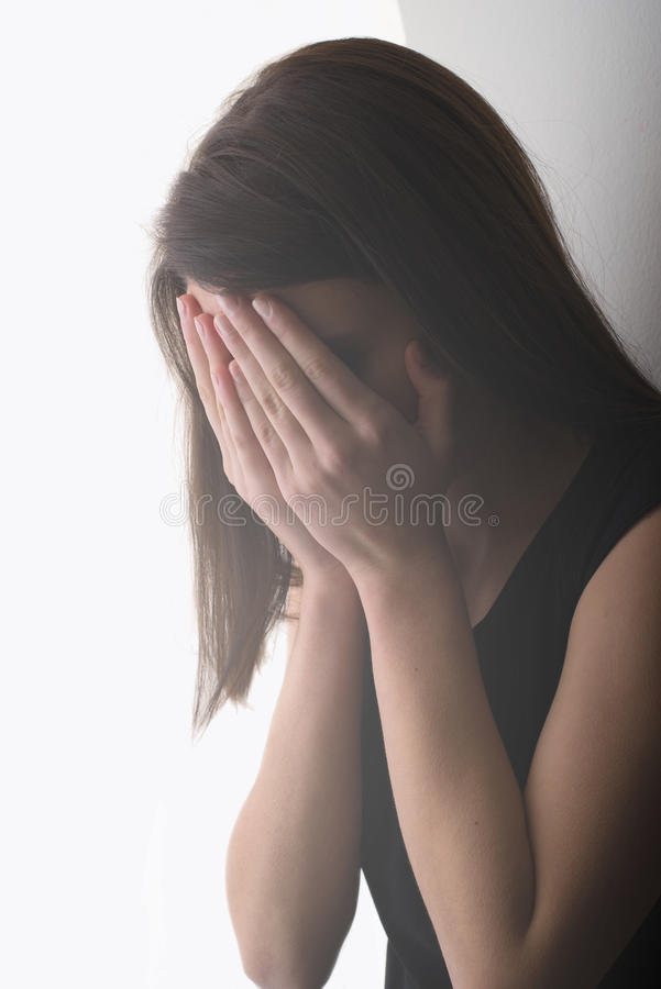 Ensam ledsen flickagråt och beläggning hennes framsida, medan stå luta arkivfoto