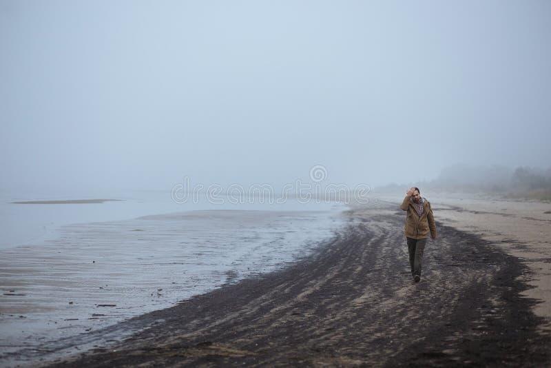 Ensam ledsen man som går på en dimmig strand royaltyfria bilder