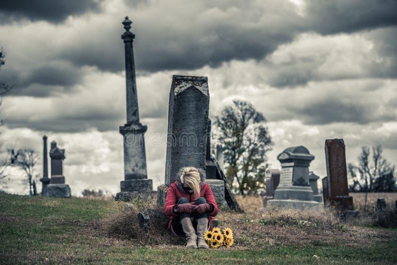 Ensam ledsen ung kvinna, i att sörja framme av en gravsten royaltyfri bild