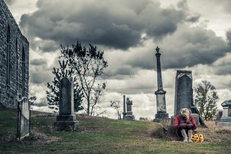 Ensam ledsen ung kvinna, i att sörja framme av en gravsten royaltyfria bilder