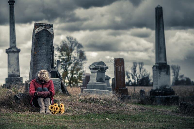 Ensam ledsen ung kvinna, i att sörja framme av en gravsten royaltyfria foton