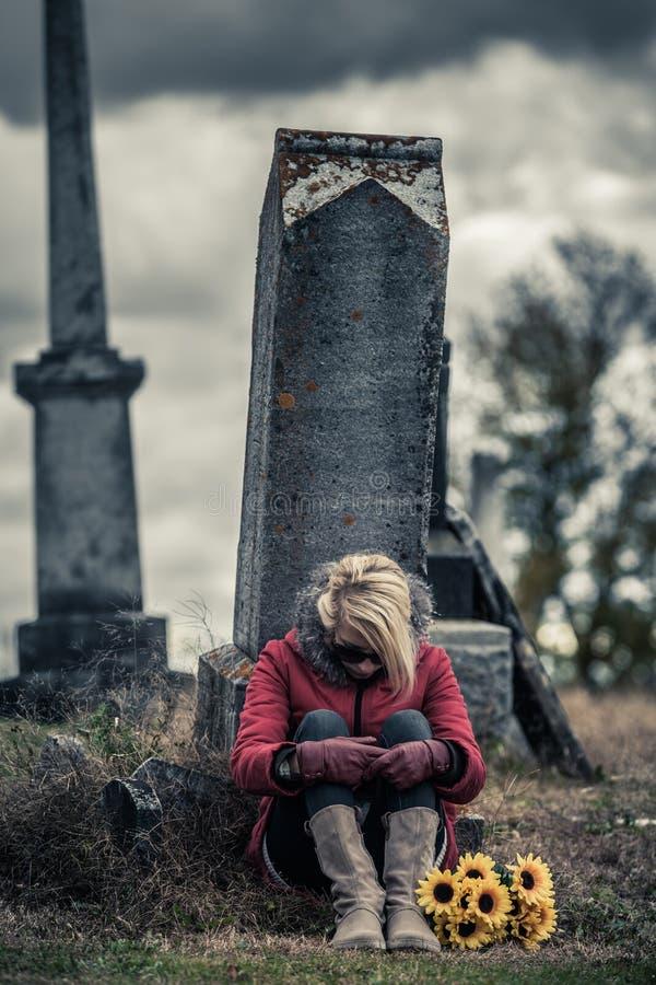Ensam ledsen ung kvinna, i att sörja framme av en gravsten arkivfoton