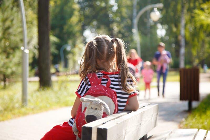 Ensam liten flicka med ett ryggsäcksammanträde på en bänk i parkera arkivbilder