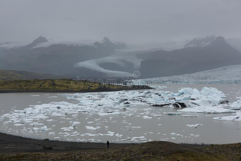 Ensam man i glaciärlagun i Island arkivfoto