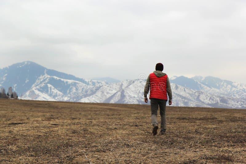 Ensam man i röd waistcoat som går in mot bergbakgrund royaltyfri bild