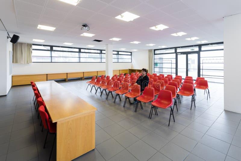 Ensam man i tomt konferensrum, begrepp arkivfoton