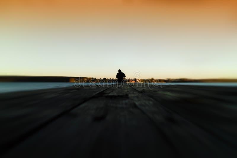 Ensam man på orange solnedgångzoom för pir royaltyfri fotografi