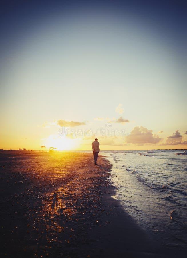 Ensam man som går på stranden på solnedgången fotografering för bildbyråer