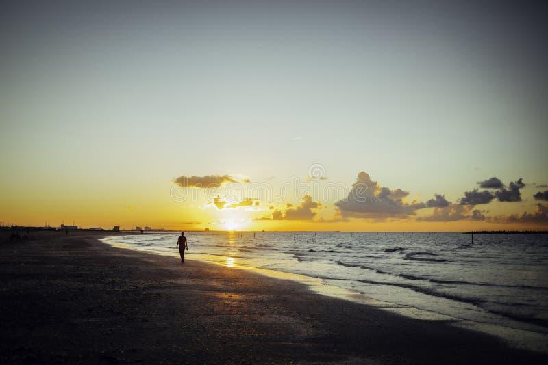 Ensam man som går på stranden på solnedgången arkivfoton