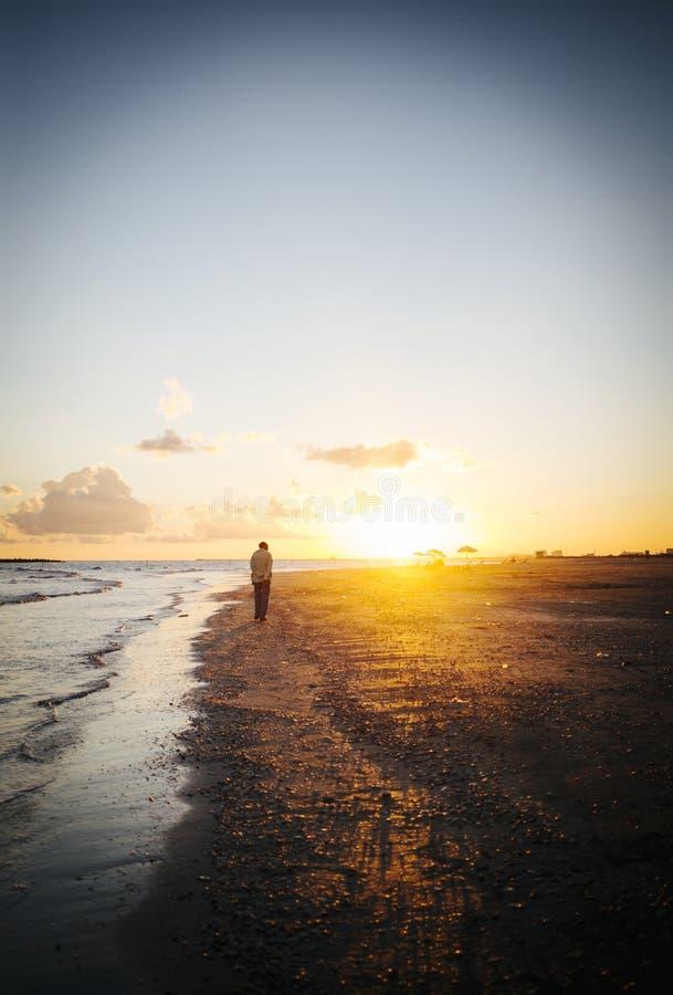 Ensam man som går på stranden på solnedgången arkivfoto