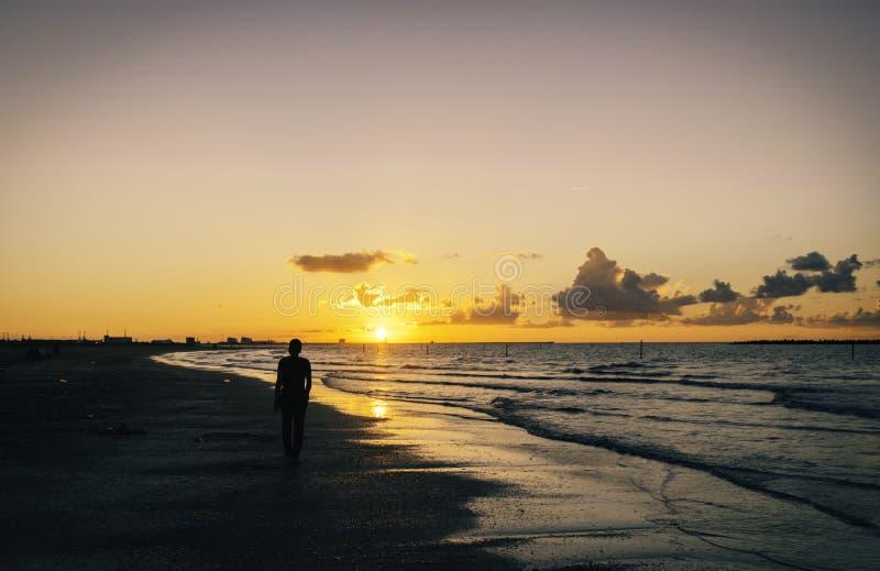 Ensam man som går på stranden på solnedgången arkivbild