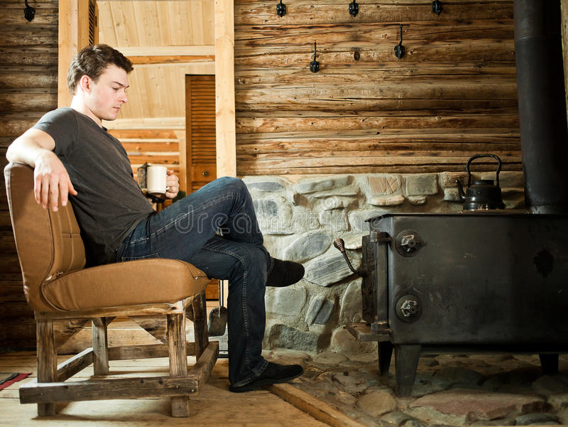 Ensam man som kopplar av med häftklammermatare och koppen kaffe arkivbilder