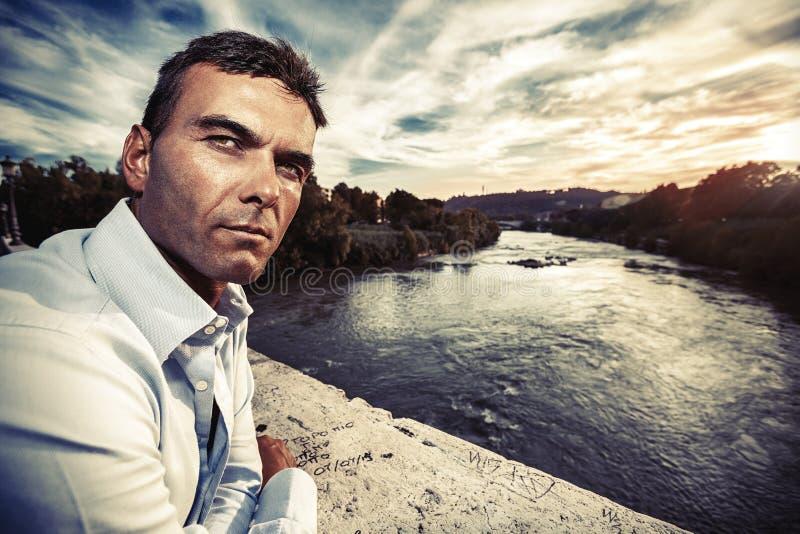 Ensam man som ser misstänksam Flod på solnedgången royaltyfri foto