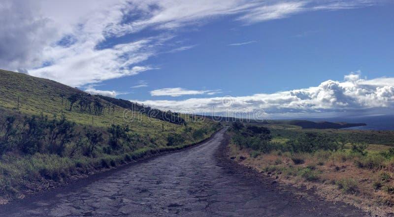 Ensam och avlägsen ojämn väg, Piilani Hwy förbi Hana runt om söder av Maui med det Haleakala berget, havet och moln i bakgrund royaltyfria foton
