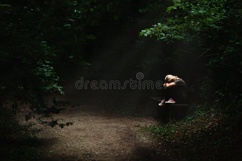 Ensam och ledsen blond kvinna som sitter på en bänk i en ljus fläck i mitt av den mörka skogbanan royaltyfria bilder