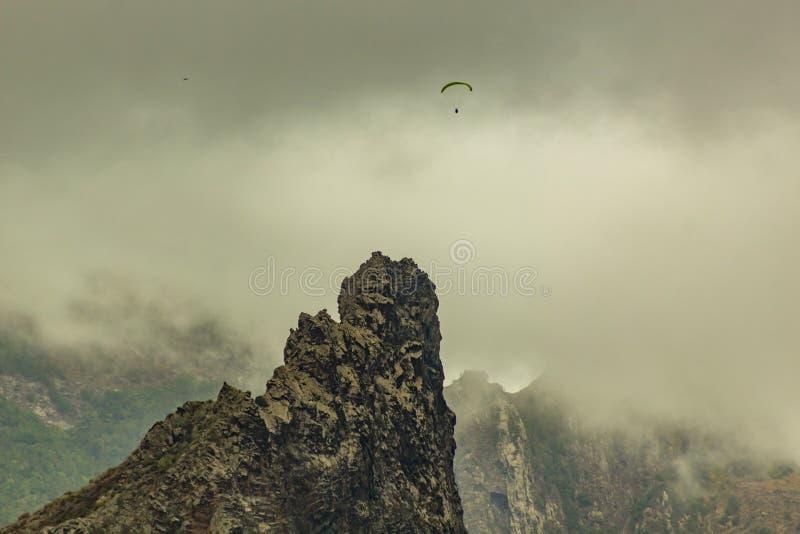 Ensam paraglider mellan det låga täta moln och bergmaximumet nära by av Garachico, Tenerife, Spanien arkivfoton