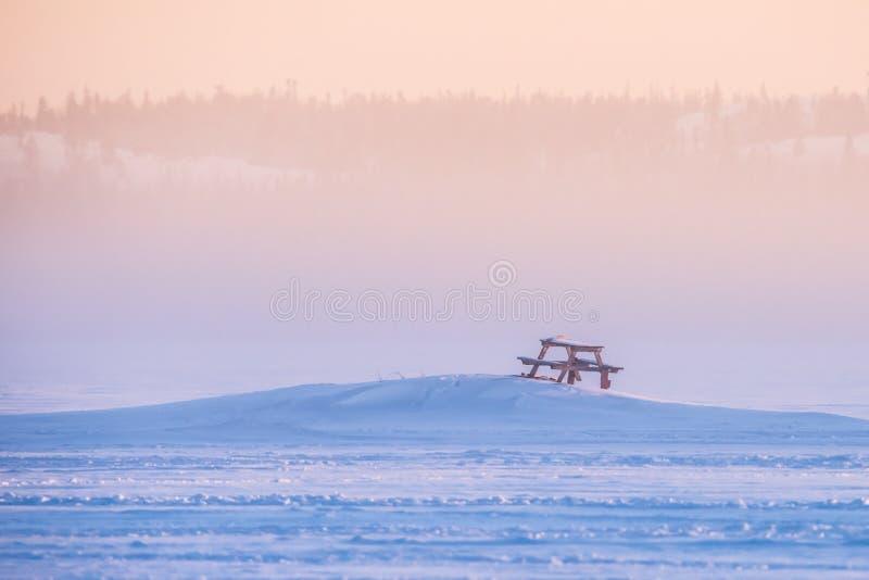 Ensam picknicktabell i snö på den djupfrysta sjön, Yellowknife arkivbild