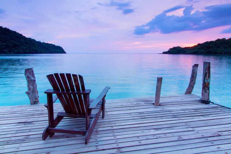 Ensam plats; Enkel trästol i porten över havet på twilien fotografering för bildbyråer