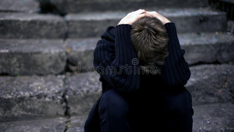 Ensam pojkegråt som sitter på gamla spruckna moment, skrämt krigbarn, hemlös royaltyfria foton