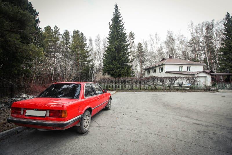 Ensam röd bil i en by arkivfoto