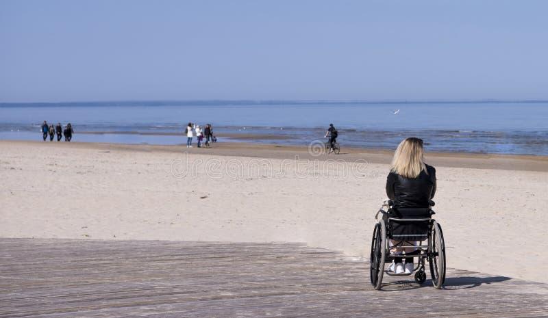 Ensam r?relsehindrad ung kvinna p? stranden solig dagsommar royaltyfri fotografi