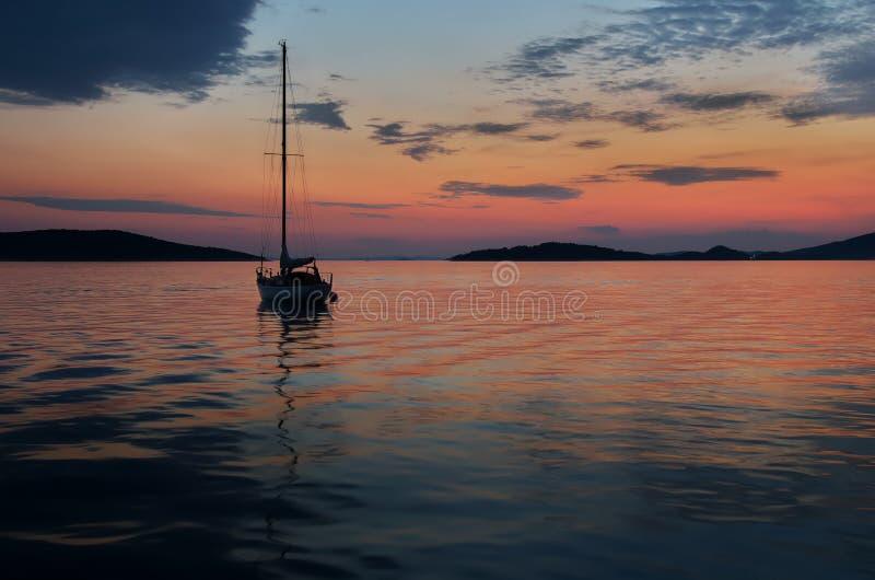 Ensam segelbåt i solnedgång nära den Prvic ön, Kroatien arkivfoton