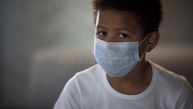 Ensam sjuk Afro--amerikan pojke i framsidamaskering på suddig bakgrund, karantän royaltyfri bild
